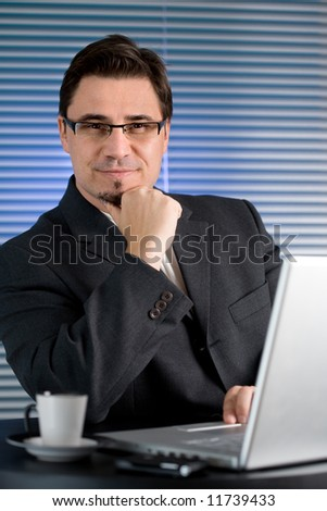 Businessman sitting at desk in office and drinking coffee. - stock photo