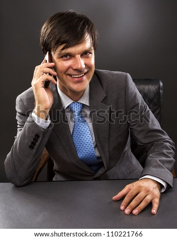 Businessman sitting at desk in office, talking on  phone, smiling.