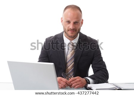 Businessman sitting at desk, over white background, working with laptop computer. - stock photo