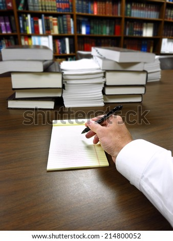 Businessman sitting at desk with pad of paper and piles fileswriting - stock photo