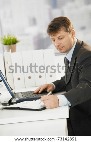 Businessman sitting at desk, writing notes to organizer and using laptop computer.? - stock photo