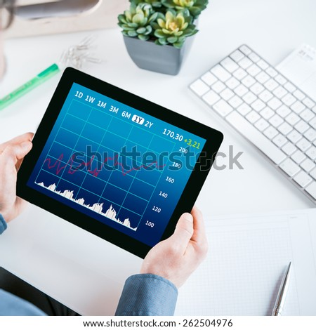 Businessman sitting at his desk n the office looking at an analytical graph on his tablet showing a time line and performance or projections, close up view of the screen and his hands - stock photo