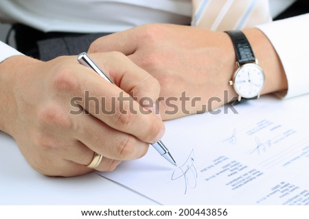 Businessman  sitting at office desk and  signing a contract  by pen - stock photo