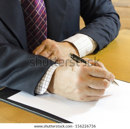 Businessman sitting at office desk signing a contract - stock photo