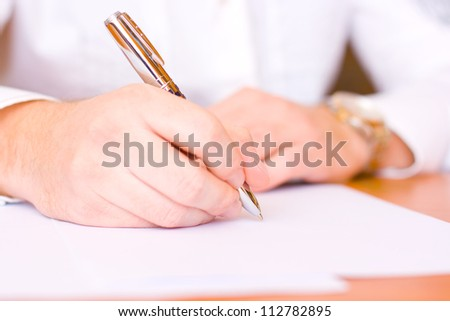 Businessman sitting at office desk signing a contract - focus on right hand with a pen