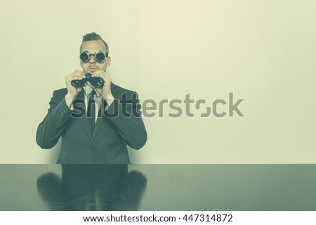 Businessman sitting at office desk with binoculars - stock photo