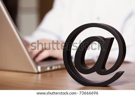 Businessman sitting at office desk working on laptop and using the internet for emailing symbolized by the stand-alone letter at symbol. - stock photo
