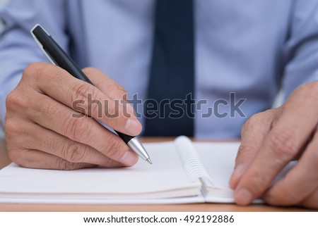 Businessman sitting at office desk writing something on paper notebook, close up.