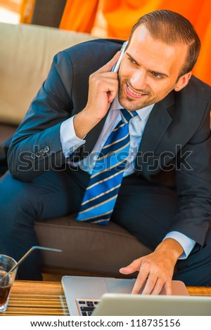 Businessman sitting at table in cafe - stock photo