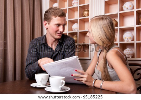 Businessman sitting at table in cafe on business lunch and showing his ideas, young businesswoman sitting near him and looking at him. - stock photo
