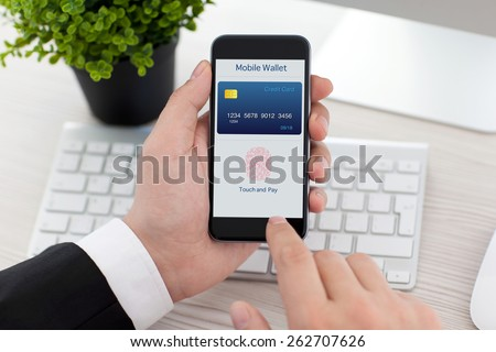 businessman sitting at the desk in office and holding phone with app mobile wallet and fingerprint for online shopping - stock photo