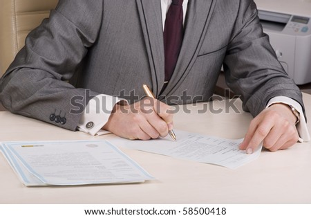 businessman sitting at the desk with blank paper and pen in hand - stock photo