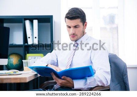 Businessman sitting at the table and reading document in office