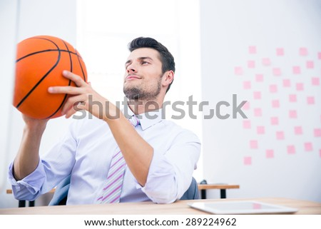 Businessman sitting at the table with ball in office - stock photo