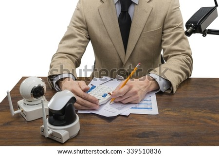 Businessman Sitting Behind the Table with Documents, Calculator and Cameras - Isolated