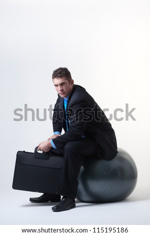 businessman sitting down on a gym fitness ball - stock photo