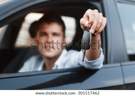 Businessman sitting in a car and giving a car key. - stock photo