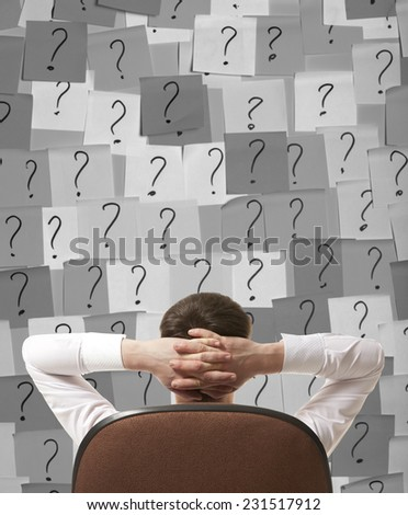 Businessman sitting in a chair, and solves the problem - stock photo