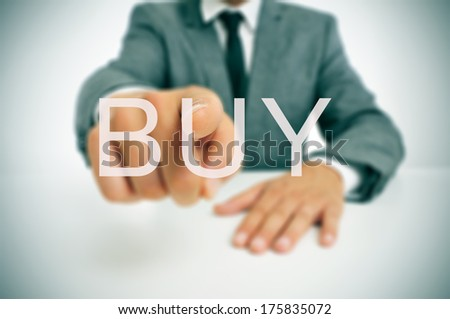 businessman sitting in a desk pointing the word buy written in the foreground - stock photo