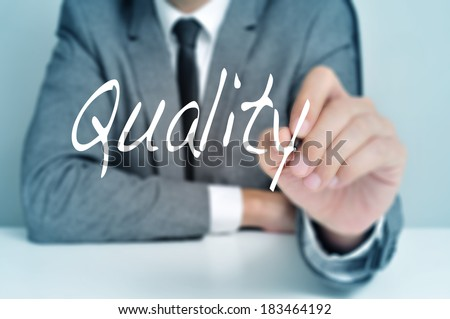 businessman sitting in a desk writing the word quality in the foreground - stock photo