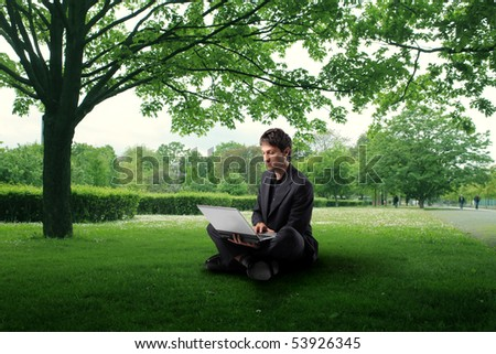 Businessman sitting in a park and using a laptop - stock photo