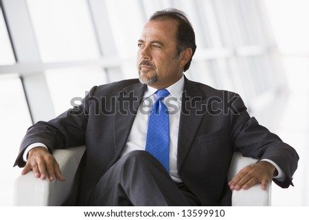 Businessman sitting in chair in office lobby - stock photo
