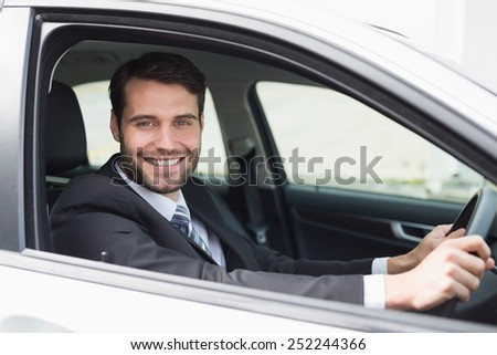 Businessman sitting in drivers seat in his car - stock photo