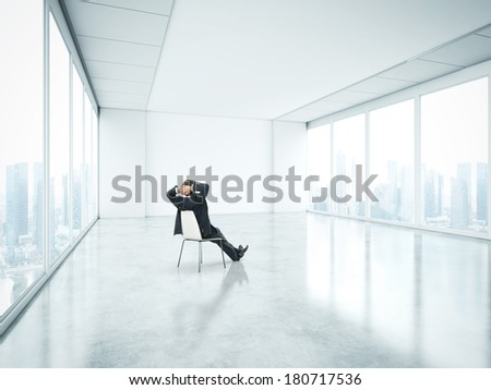 Businessman sitting in empty bright office and look at city