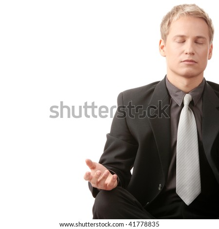 Businessman sitting in lotus position isolated - stock photo