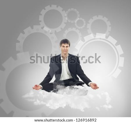 Businessman sitting in lotus position on a cloud and think mechanical thoughts - stock photo