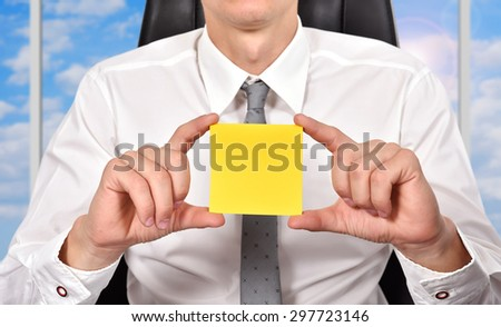 businessman sitting in office and holding yellow paper