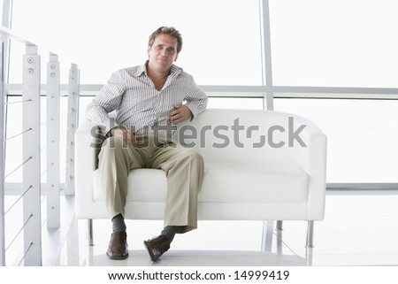 Businessman sitting in office lobby - stock photo
