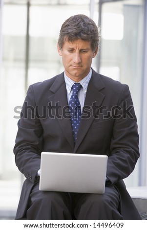 Businessman sitting in office lobby using laptop - stock photo