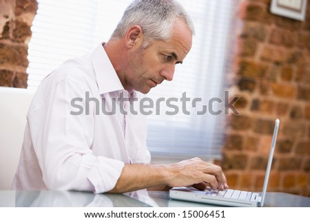 Businessman sitting in office typing on laptop - stock photo