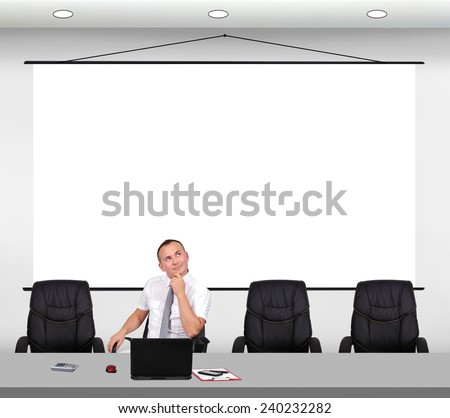 businessman sitting in office with big poster on wall - stock photo