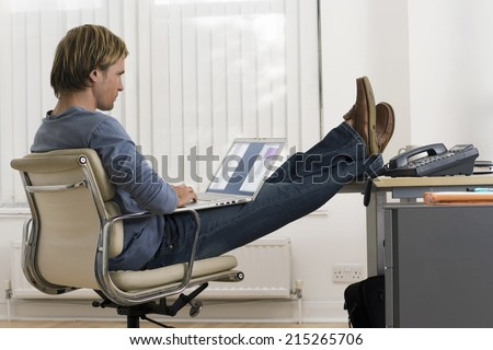 Businessman sitting in office with feet up on desk, using laptop in lap, profile - stock photo