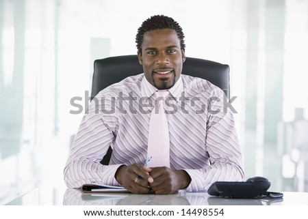 Businessman sitting in office with personal organizer smiling - stock photo