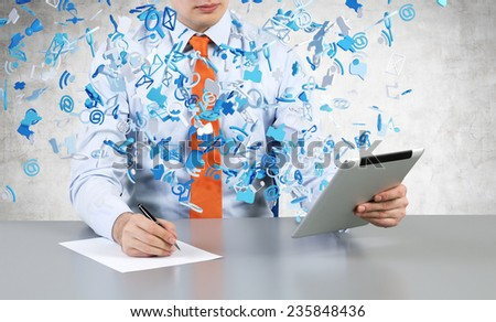 businessman sitting in office with tablet and drawing on paper - stock photo