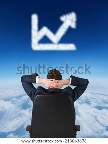 Businessman sitting in swivel chair against blue sky over clouds at high altitude - stock photo