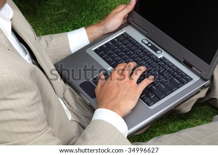 Businessman sitting in the grass using a laptop - stock photo