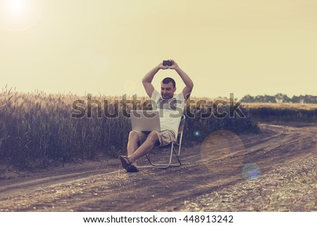 Businessman sitting in the middle of the field and working on laptop and talking on the phone. Relax and work. Outdoor work. In the nature. Successful deal. - stock photo
