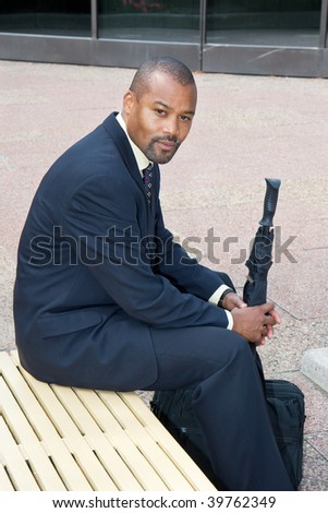 businessman sitting on a bench in a courtyard