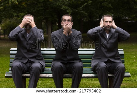 businessman sitting on a bench three times covering his ears,eyes and mouth - stock photo