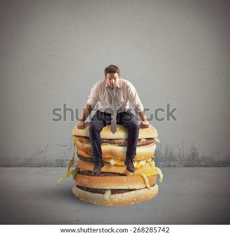Businessman sitting on a big double sandwich - stock photo