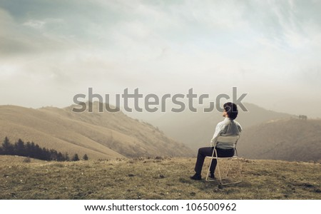Businessman sitting on a chair and observing the panorama - stock photo