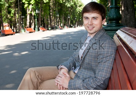 businessman sitting on a park bench, resting, smiling