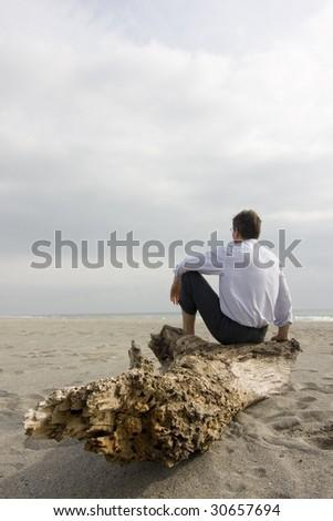 Businessman sitting on a tree trunk on a beach - stock photo