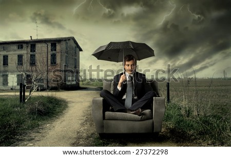businessman sitting on armchair with umbrella in the countryside - stock photo