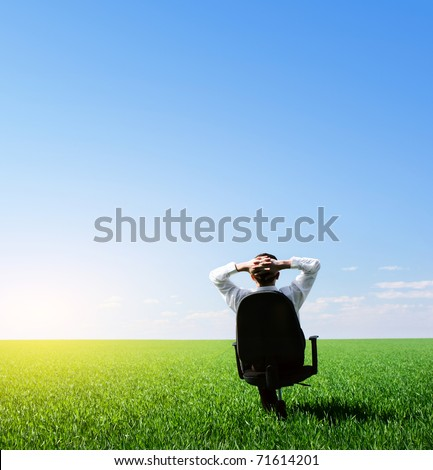 Businessman sitting on chair in green meadow and looking to a blue clear sky - stock photo