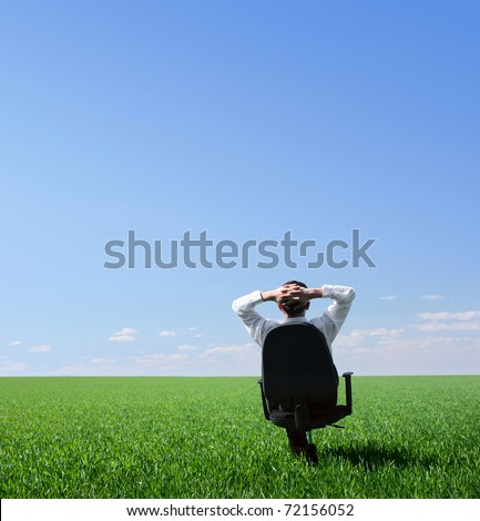 Businessman sitting on chair in green meadow and looking to a blue clear sky